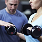 Healthy Female Lifting Weights with Trainer